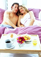 view of a breakfast tray on a bed and a young couple sitting together
