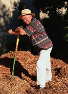 Side profile of an elderly man leaning on a rake in a pile of leaves