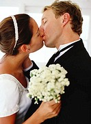 side view of a bride and groom kissing each other