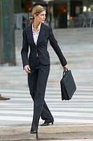 businesswoman looking over her shoulder carrying a briefcase