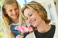 daughter (10-11) giving a flower to her mother