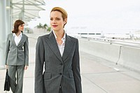 Two businesswomen walking down the street and one of them carrying a briefcase