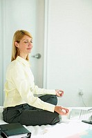 side view of a businesswoman in a yoga position on the bed with the laptop in front of her