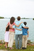 rear view of a family with their arms around each other looking out at a lake
