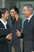 Two business executives talking in the foreground and another businesswoman talking on mobile phone in the background