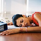 close-up of a woman asleep on her office desk