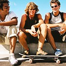 portrait of three young men sitting on a wall with a skateboard