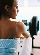 close-up of the back of a woman sitting in a gym