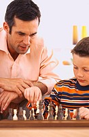Close-up of a young man playing chess with his son (6-8)