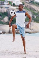 Side profile of a young man hitting a football on the beach