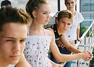 close-up of a group of teenage boys and girls leaning on a railing of a balcony