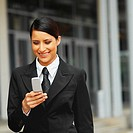 Front view of a smiling businesswoman using a mobile phone