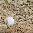 Close-up of a golf ball in a bunker