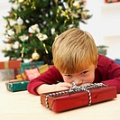 Boy (5-6) lying on the floor with a Christmas present