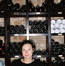portrait of a woman standing in a wine cellar