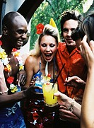 view of a group of friends holding straws admiring a cocktail