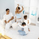 Close-up of parents and two children jumping on bed (9-11)