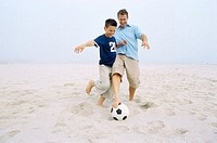 Father and son (10-11) playing football on the beach