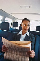 Young businesswoman sitting in the back of a vehicle reading a newspaper