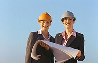 Front view portrait of two business executives holding blueprint and wearing hard hats