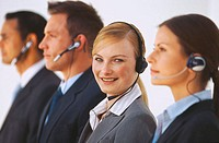 Group of business executives standing in a row wearing headsets