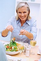 Portrait of a woman serving salad at a dinner table
