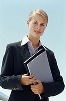 Front view portrait of businesswoman holding notebook and diary