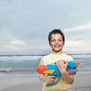 Front view portrait of boy holding water gun (10-11)