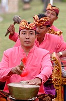 three balinese musicians playing gamelan
