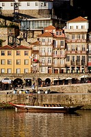 Porto, Portugal: Ancient-looking boat with empty casks of port wine advertises port-wine tasting lodges on south bank of the Rio Douro. The north bank...
