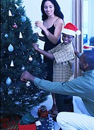 portrait of a young couple with their son decorating a Christmas tree