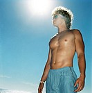 low angle view of a bare chested man standing under the sun