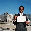 portrait of a businessman holding up a blank sheet of paper