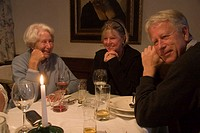 Fraueninsel, Chiemsee, Bavaria, Germany. A family sits around the dinner table at a restaurant.