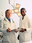 Portrait of two male doctors standing holding a clipboard