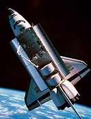 The space shuttle with cargo bay open orbiting above earth