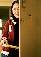 Close-up of a young woman leaning on a school locker and holding a book