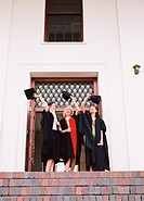 Low angle view of three female graduates taking their hats off
