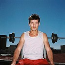 Portrait of a young man sitting on a weight lifting bench looking at camera