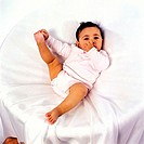 Elevated view of a baby (12-18 months) holding his feet