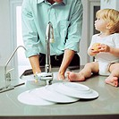 Close-up of a young man washing his hands with a baby (12-18 months) sitting on the counter