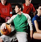 Group of young people sitting together holding a basketball