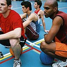 Close-up of a group of young men sitting in a basketball court