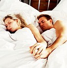 Close-up of a couple sleeping in bed holding hands