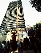 Low angle view of a group of people standing near a high rise building