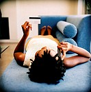 Young woman lying on a couch talking on a mobile phone