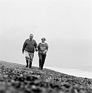 Elderly couple walking on the beach (black and white)