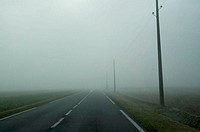 Road through foggy landscape, Normandie, France