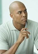 Man holding pen to chin, portrait