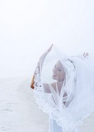 Bride holding up veil on beach